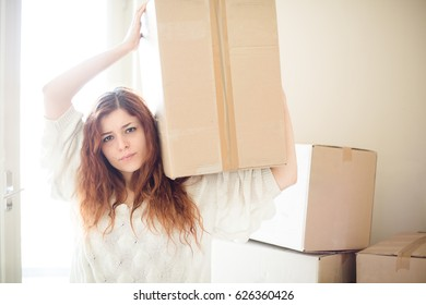 Tired Redhead Woman Moving, Holding a Box on Her Shoulder