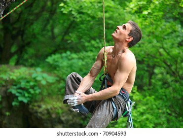Tired rock climber hanging on the rope and looking up after falling off from the route