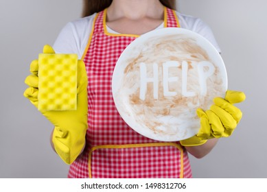 Tired of routine at home concept. Cropped close up photo of woman with crying face holding showing smeared in sauce chocolate dessert plate trying to remove the dirt isolated grey background
