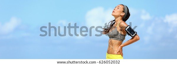 Tired runner exhausted after cardio exercise run in summer sun banner with sky background. Asian running woman working out breathing hard listening to music with phone app.