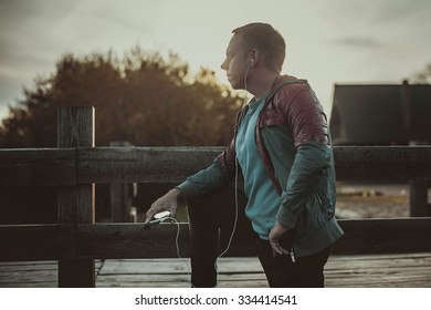 tired runner standing, relaxing and listening to music your phone on a wooden pier, sport.