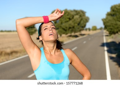 Tired runner sweating after running hard in countryside road. Exhausted sweaty woman after marathon training on hot summer. Hispanic brunette female athlete outdoors.