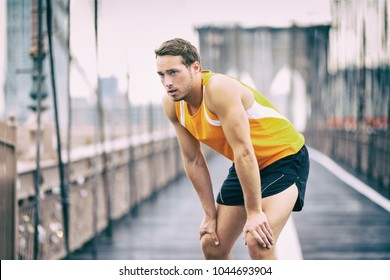 Tired runner taking a break breathing during jogging workout training on Brooklyn bridge in New York City, NYC active healthy lifestyle. Man running outdoors.