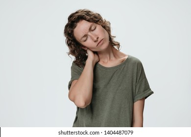 Tired sad young woman suffering from fatigued massaging hurt stiff neck rubbing tensed muscles to relieve joint pain. Symptom of cervical chondrosis. Inflammation of vertebra, fibromyalgia concept