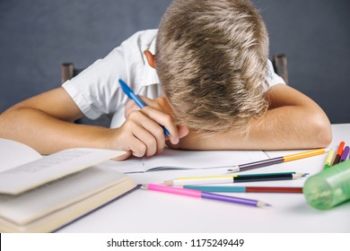 Tired schoolboy fell asleep for lessons. The student does homework.