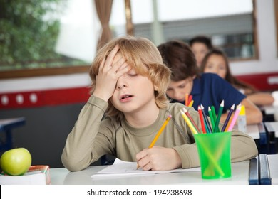 Tired schoolboy with hand on face sitting at desk in classroom