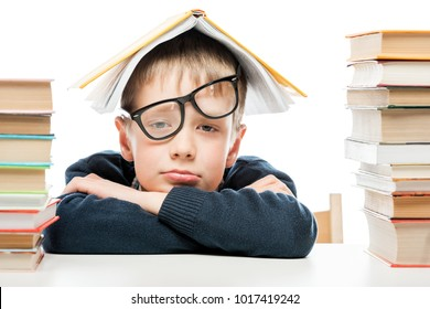 tired schoolboy and piles of books on white background, close-up portrait