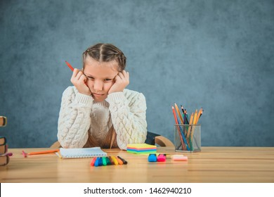 Tired schoolgirl leans down and puts her head down and undersetting head with hands. Little girl is compressing red pencil on grey background.