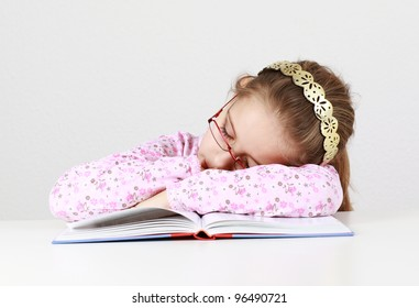 Tired schoolgirl sleeping on book instead of learning