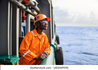 Tired Seaman AB or Bosun on deck of vessel or ship , wearing PPE personal protective equipment - helmet, coverall, lifejacket, goggles. Safety at sea