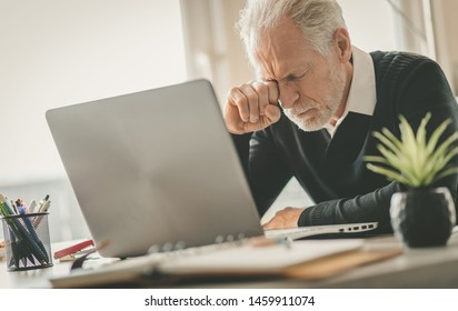Tired senior businessman rubbing his eyes sitting in office