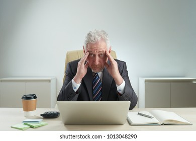 Tired senior white collar worker looking at camera while rubbing his temples and sitting at office desk, waist-up portrait shot