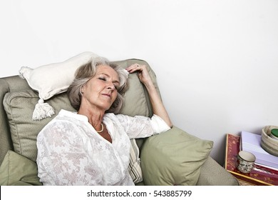 Tired senior woman sleeping on armchair at home