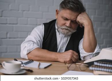 tired senior writer sleeping at workplace