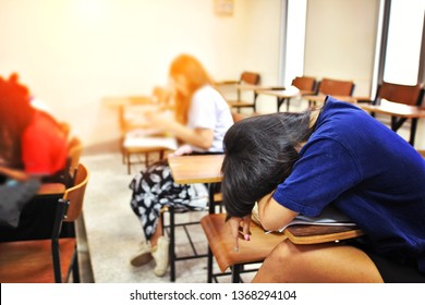 A tired and sick student sleeps in classroom while studying or taking a lecture - education, academic or business concept of boring classroom course or uninteresting training program, selective focus