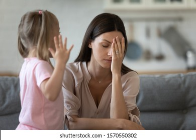 Tired single mother feel stressed desperate about screaming stubborn kid daughter tantrum, frustrated depressed young adult mom annoyed by naughty difficult rebellious child girl problems concept