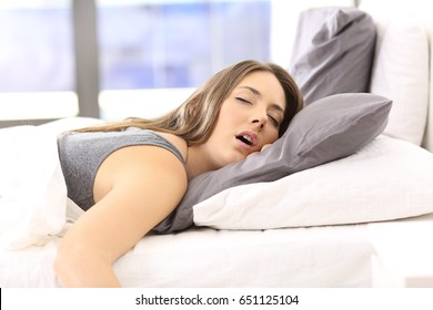 Tired single woman resting on the bed of an hotel room or home