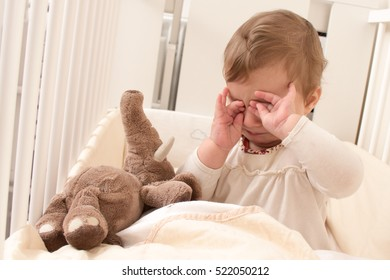Tired sleepy 8 months old  baby from Slovenia with teddy bear sitting in bed and rubbing eyes before going to sleep