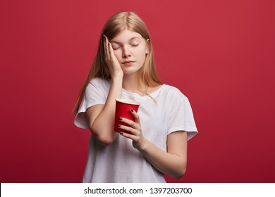 tired sleepy beautiful woman with closed eyes covers her cheek with palm, holding coffee. close up photo. tiredness concept