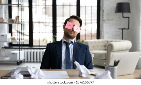 Tired sleepy businessman with stickers, adhesive notes on eyes sleeping at workplace, sitting at work desk in office, unproductive lazy employee executive dozing, working on difficult project