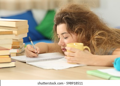 Tired and sleepy student with tousled hair trying to write notes on a desk in her room in a house indoor