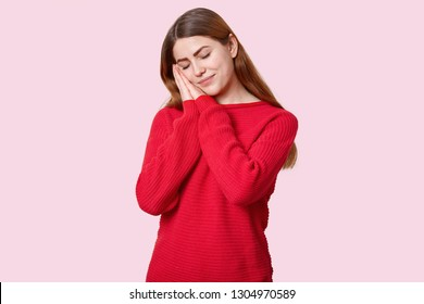 Tired sleepy woman takes nap leans on palms, has eyes closed, dressed in red jumper, wants to have rest, enjoys calm atmosphere, isolated over rosy background. People, relaxation and sleeping