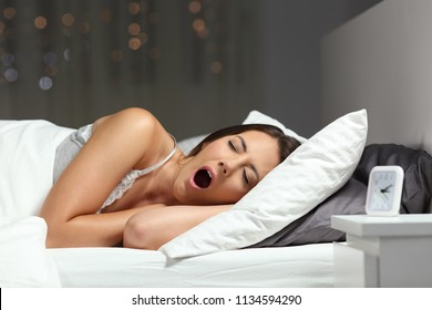 Tired sleepy woman yawning ready to sleep on a bed in the night at home