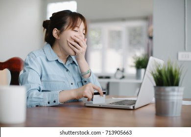 Tired sleepy woman yawning, working at office desk and holding credit card, overwork and sleep deprivation concept