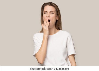 Tired sleepy young woman yawning, covering mouth with hand, exhausted bored female looking at camera, feeling lazy, suffering from lack of sleep and energy, isolated on grey studio background