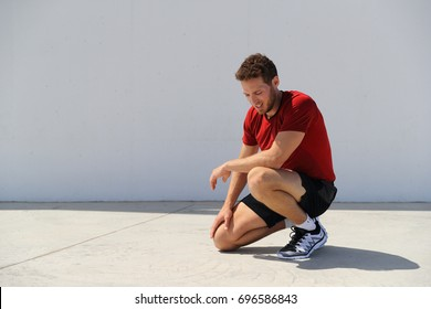 Tired sport fitness man exhausted breathing after difficult workout outdoors. Heat exhaustion athlete dehydrated or runner with knee injury pain resting in disappointment.