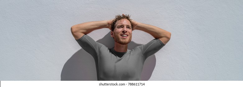 Tired sport man exhausted breathing with difficulty after fitness training resting with arms on head. Headache, dehydration concept. Athlete sweating in summer, sun or heat stroke banner panorama.