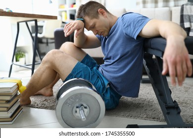 Tired from sports exercises guy sits floor at home. Useful space in apartment for sports. Fatigue from physical exertion. Sports injury at home. Loss motivation during self-isolation