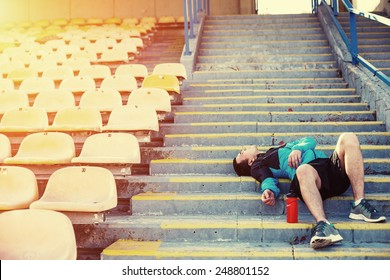 tired sportsman lying on the stairs and resting at stadium