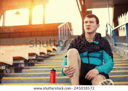 tired sportsman resting with a bottle of water sitting on the stairs at stadium