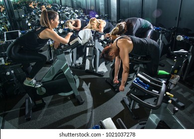 Tired sporty women after hard spinning workout class at gym.