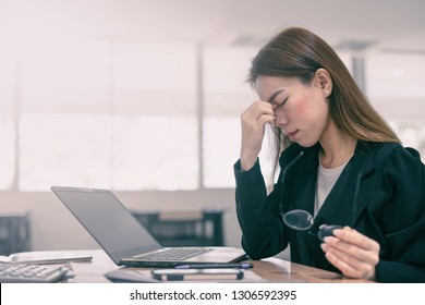Tired and stressed asian business woman closed eyes massaging nose and sitting at desk in front of laptop at office background
