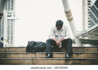 Tired or stressed businessman sitting on the walkway in the city after his work. Image of Stressed businessman concept.
