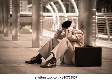Tired or stressed businessman sitting on the walkway in the modern city after his work. Image of Stressed business concept.