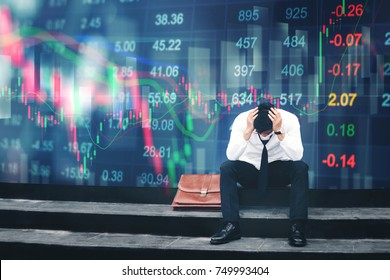 Tired or stressed businessman sitting on the walkway in panic digital stock market financial background