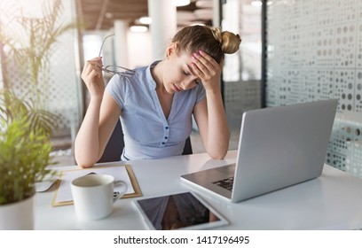Tired, stressed businesswoman at laptop in office