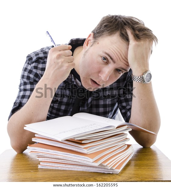 Tired, stressed male teacher marking books. Isolated image on white background.