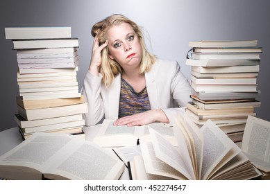 Tired, stressed and overworked adult student. Young overwhelmed woman studying hard. Female model between a huge pile of books.