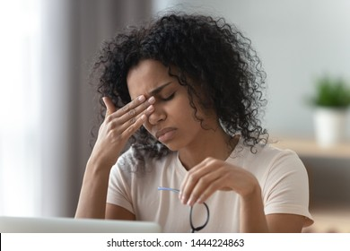 Tired stressed overworked young african woman student feel hurt fatigue eye strain headache after computer work take off glasses suffer from pain in dry eyes, bad vision problem, eyestrain concept