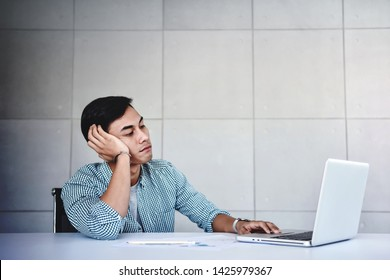 Tired and Stressed Young Businessman Sitting on Desk in Office with Computer Laptop. Exhausted Man Boring a Hard Work