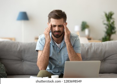 Tired stressed young man suffering from headache attack after computer work on laptop feeling fatigue at home, overworked exhausted guy massaging temples to relieve pain from migraine high pressure