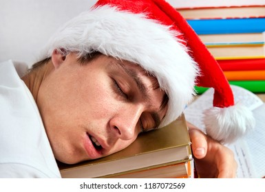 Tired Student in Santa Hat sleep on the Books closeup