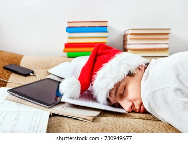 Tired Student in Santa's Hat sleeping on the Couch