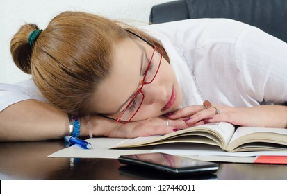 Tired student sleeping on the books instead of studying.