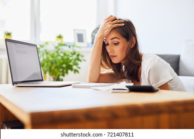 Tired student struggling to keep studying looking at notes and laptop