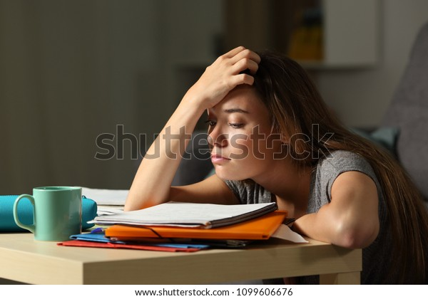 Tired student trying to study in the night at home